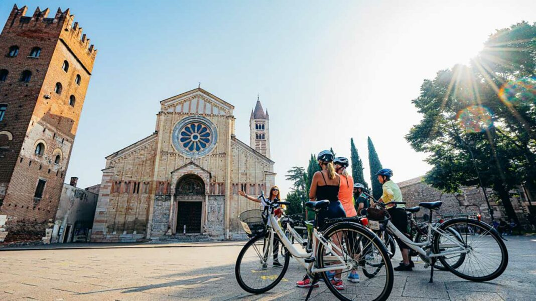 Verona by bike. On the background the Duomo in Verona